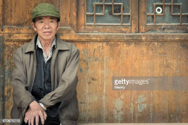 Chinese Senior Man sitting on bench in front of his home in Zhaoxing China