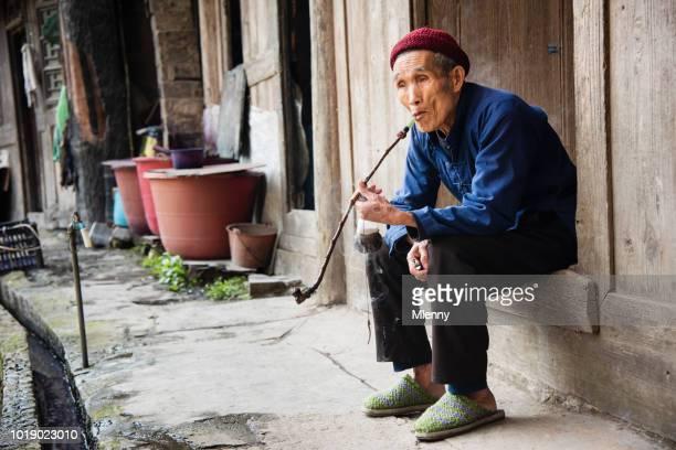 Chinesische senior woman Pfeife Haustüre in seinem Dorf