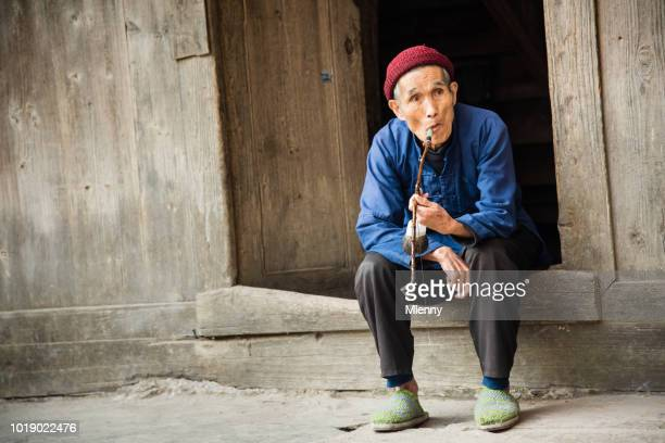 Chinesische senior woman Pfeife in seinem Homedoor in Zhao Xing