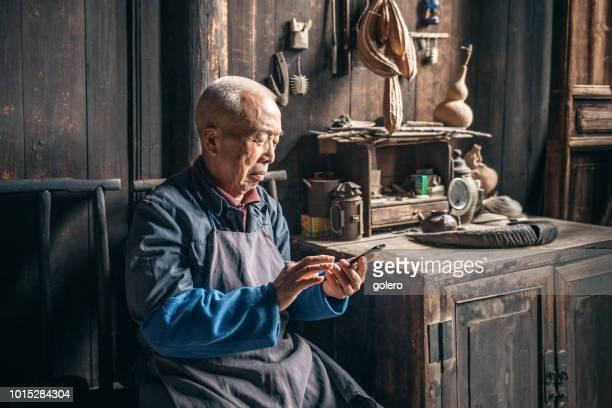 chinese senior man te tikken op mobiel in houten huis - chinese cultuur stockfoto's en -beelden