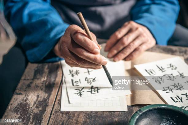 chinese senior man writing chinese calligraphy characters on paper - non western script stock pictures, royalty-free photos & images