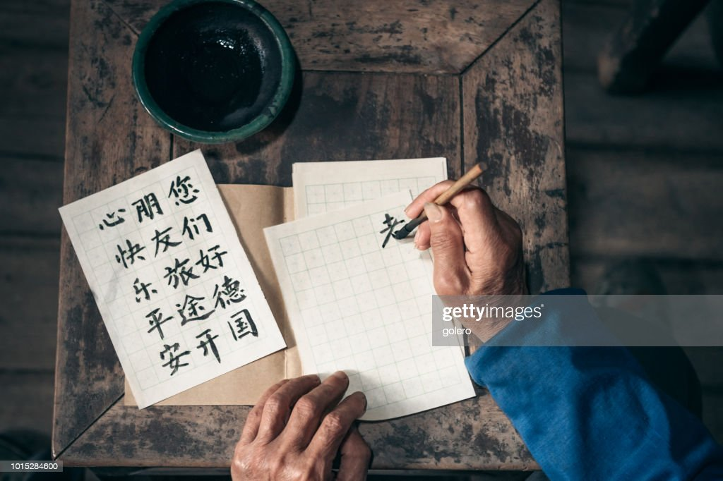 chinese senior man writing chinese calligraphy characters on paper : Stock Photo