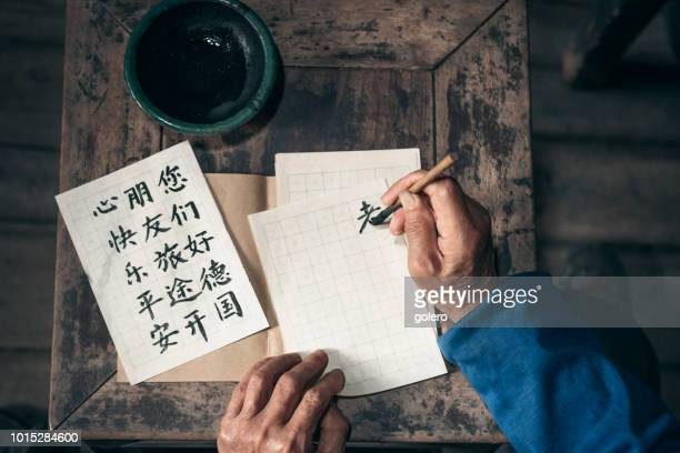 chinese senior man writing chinese calligraphy characters on paper - chinese culture stock pictures, royalty-free photos & images