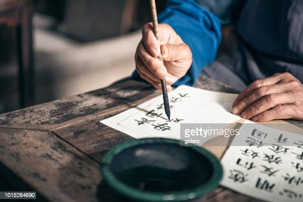 chinese senior man writing chinese calligraphy characters on paper - scrittura non occidentale foto e immagini stock