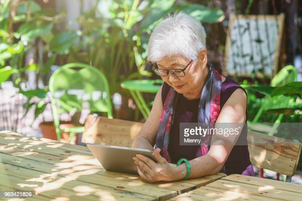 Chinese senior woman with tablet computer in Kuala Lumpur Cafe