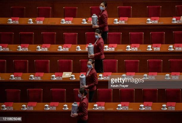 Chinese servers wear protective masks as they prepare tea for delegates before the closing session of the National People's Congress at the Great...