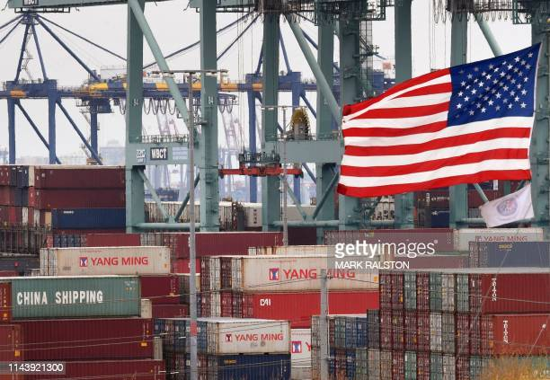 Chinese shipping containers are stored beside a US flag after they were unloaded at the Port of Los Angeles in Long Beach California on May 14 2019...