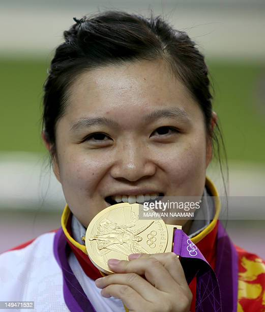 Chinese shooter Guo Wenjun winner of the gold medal of the women's 10m Air Pistol at the London 2012 Olympic Games bites her medal at The Royal...