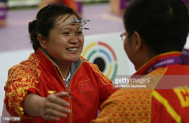 Chinese shooter Guo Wenjun winner of the gold medal of the women's 10m Air Pistol at the London 2012 Olympic Games embraces her coach as she...