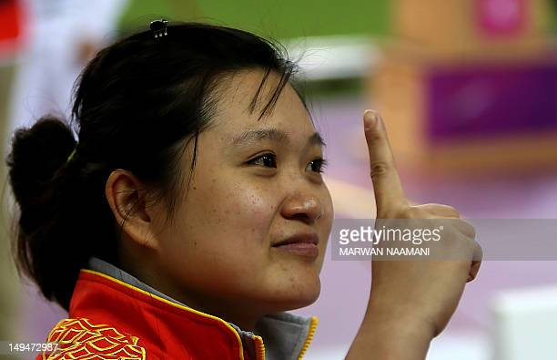 Chinese shooter Guo Wenjun winner of the gold medal of the women's 10m Air Pistol at the London 2012 Olympic Games gestures as she celebrates her...