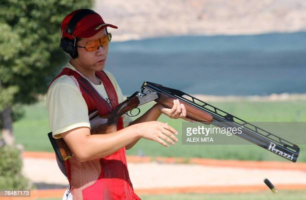 Chinese shooter Qiang Pan takes discharges his spent shells during the double trap competition of the first day of the ISSF World Shooting...