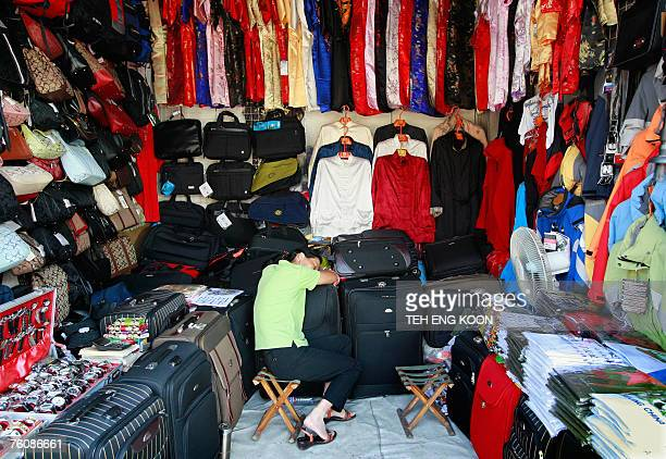 Chinese shop assistant takes a nap as she waits for customers at a shop in central Beijing, 14 August 2007. Chinese retail sales, a key gauge of...