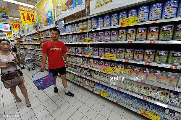 Chinese shoppers pass tins of milk powder on sale at a supermarket in Hefei east China's Anhui province on September 26 2010 China has moved to step...