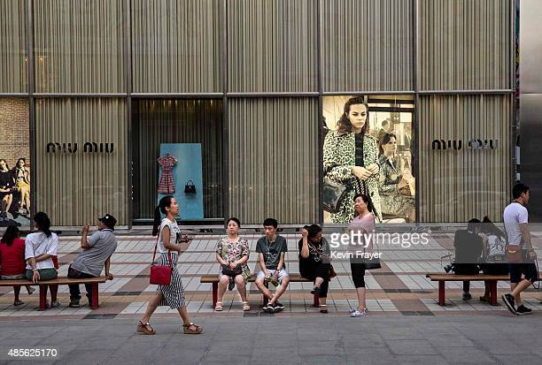 Chinese shoppers sit in front of a luxury store in an upscale shopping district on August 28 2015 in Beijing China China's government is relying on...