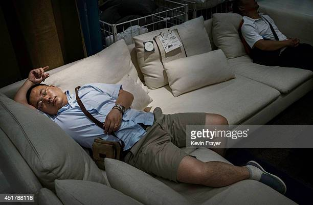 Chinese shoppers sleep on a sofa in the showroom of the IKEA store on July 6 2014 in Beijing China Of the world's ten biggest Ikea stores 8 of them...