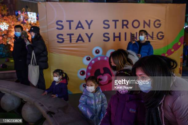 """Chinese shoppers stand next to a billboard saying """"Stay Strong"""" near an ice skating rink at a festive market at a shopping mall on December 20, 2020..."""