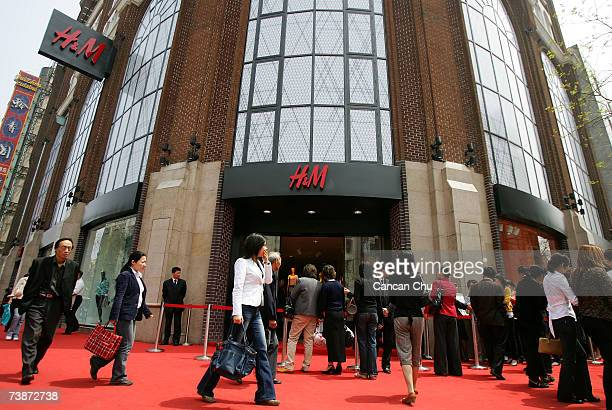 Chinese shoppers wait in line to enter the newly opened HM store the first in mainland China on April 13 2007 in Shanghai China Australian pop singer...