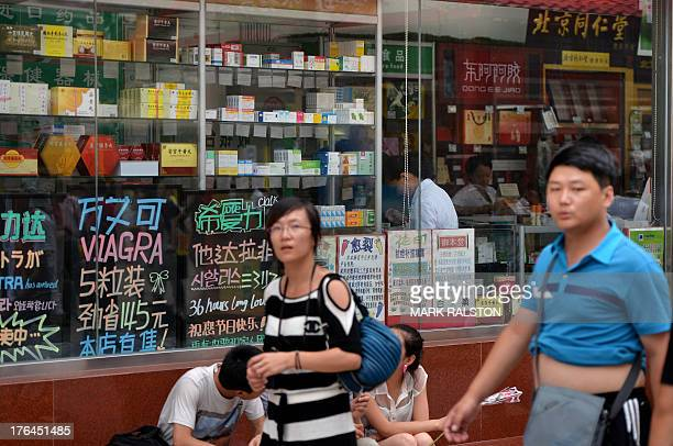 Chinese shoppers walk past a pharmacy selling medicine in Beijing on August 13 2013 Beijing city health and corruption officials have launched an...