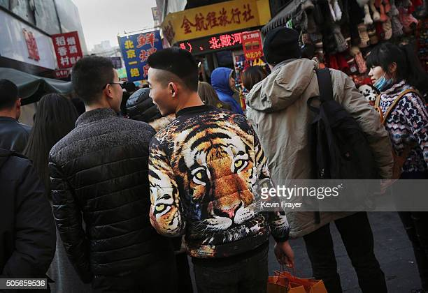 Chinese shoppers walk through a market on January 19 2016 in Beijing China In 2015 China's economy grew at its slowest rate in a quarter century data...