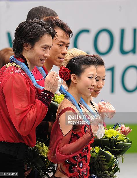 Chinese skaters Xue Shen and Hongbo Zhao and Qing Pang and Jian Tong pose on the podium after taking the gold and silver medals after the figure...