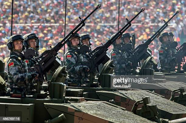 Chinese sldiers ride in an armoured vehicle as they pass in front of Tiananmen Square and the Forbidden City during a military parade on September 3...