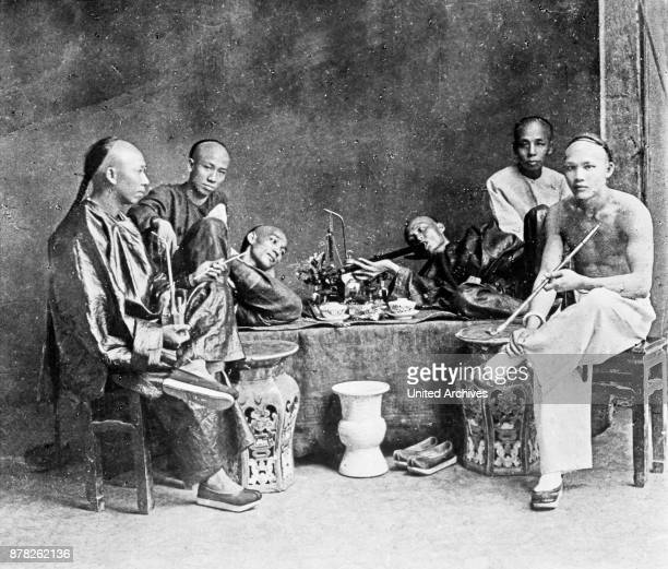 Chinese smoking in an opium den, China 1910s.