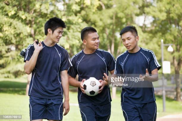 Chinese soccer players carrying ball in park