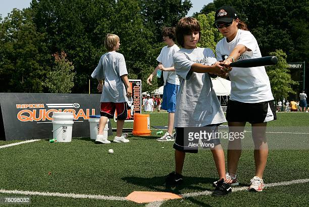 Chinese softball coach Zhang Xinyan of Shanghai practices a training technique with a young US baseball player as Zhang participates in a coaching...