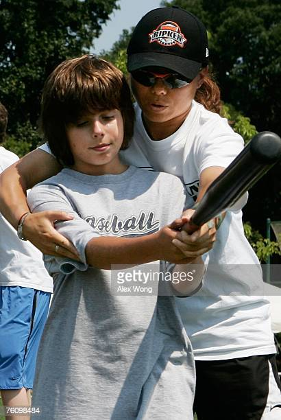 Chinese softball coach Zhang Xinyan of Shanghai practices training technique with a young US baseball player as Zhang participates in a coaching...