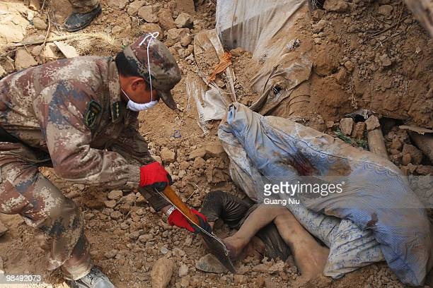 Chinese soldier digs rubble to remove a body from a collapsed building following a strong earthquake, on April 16, 2010 in Jiegu, near Golmud, China....