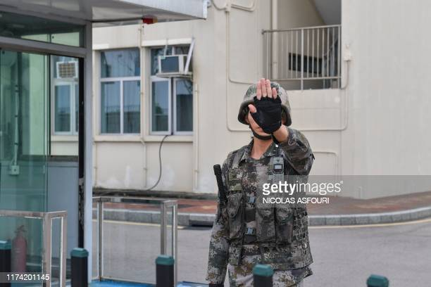 A Chinese soldier gestures at an entrance to the headquarters of the People's Liberation Army in the Admiralty district in Hong Kong on October 7...