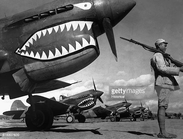 "Chinese soldier guards a line of American P-40 fighter planes, painted with the shark-face emblem of the ""Flying Tigers,"" at a flying field in China...."