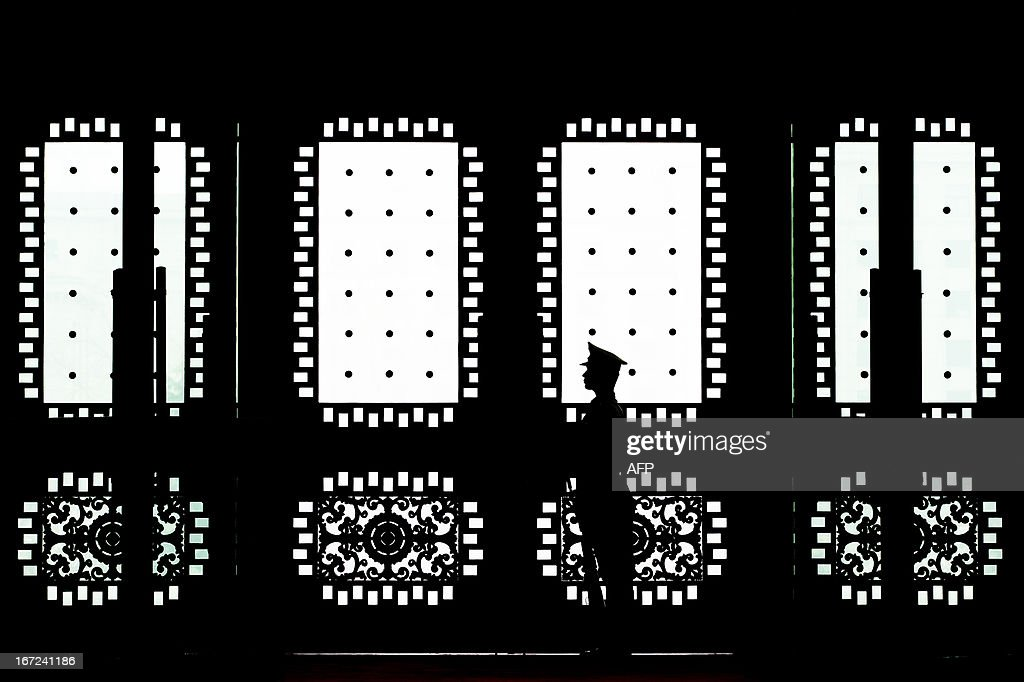 A Chinese soldier stands guard at the main entrance door of the Bayi building where US Joint Chiefs Chairman General Martin Dempsey met with Chinese military officials in Beijing on April 23, 2013. Dempsey was expected to discuss concerns over tensions with North Korea, amongst other bilateral items. AFP PHOTO / POOL / Andy Wong