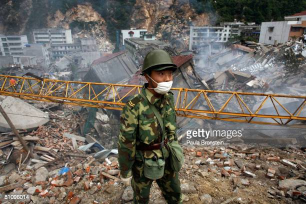 Chinese soldier stands on top of a mountain of rubble in the quake ravaged town where thousands are dead or missing May 15 2008 in Beichuan Sichuan...