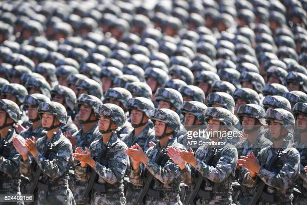 TOPSHOT Chinese soldiers applaud during a military parade at the Zhurihe training base in China's northern Inner Mongolia region on July 30 2017...