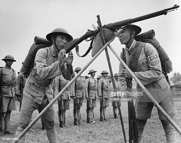 A Chinese soldiers carefully aims a rifle balanced on a tripod during rifle practice ca 1939