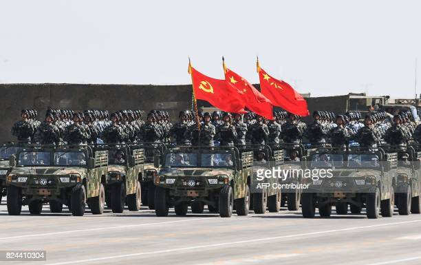 Chinese soldiers carry the flags of the Communist Party the state and the People's Liberation Army during a military parade at the Zhurihe training...
