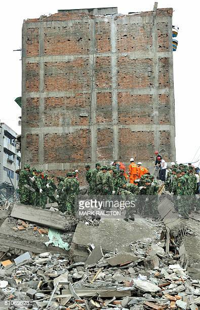 Chinese soldiers clear rubble from a collapsed building a day after a 78 magnitude earthquake hit the town of Mianzhu in Sichuan Province on May 13...