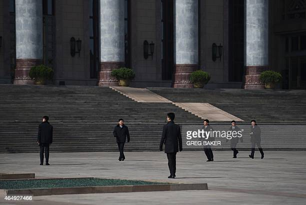 Chinese soldiers dressed as ushers clear the area in front of the Great Hall of the People in Beijing after a meeting of officials on March 2, 2015....
