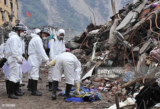 Chinese soldiers dressed in protective suits check a dead body next to rubbles at Yingxiu town of the Wenchuan county in China's southwestern...