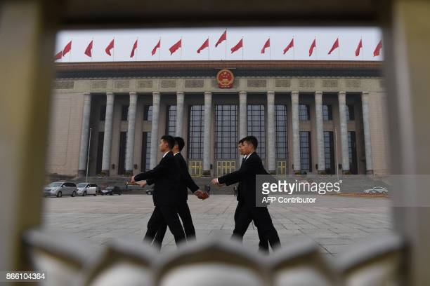 Chinese soldiers dressed in suits march outside the Great Hall of the People in Beijing, before the introduction of the Communist Party of China's...