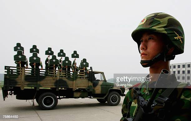 Chinese soldiers from the People's Liberation Army 196th Infantry Brigade hold up targets used for shooting practice during a performance to...