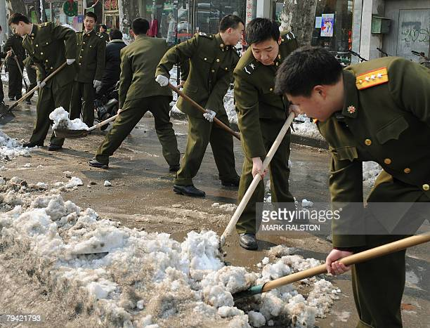 Chinese soldiers including a senior officer shovel snow from the main shopping street of the eastern Chinese city of Nanjing 31 January 2008 China...