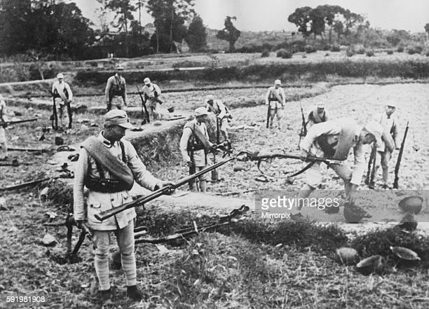 Chinese soldiers pick up the discarded weapons of Japanese soldiers who have fled from the shambles of Changsha during the Second World War. The...
