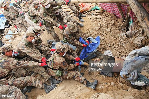 Chinese soldiers remove a body from the rubble of a collapsed building following a strong earthquake, on April 16 in Jiegu, near Golmud, China. It is...