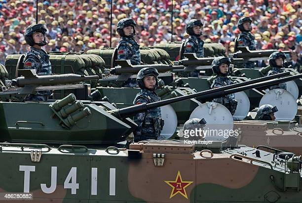 Chinese soldiers ride in armoured vehicles as they pass in front of Tiananmen Square and the Forbidden City during a military parade on September 3...