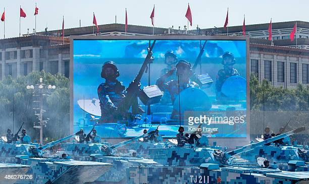 Chinese soldiers ride in tanks as they are seen on a big screen as they pass in front of Tiananmen Square and the Forbidden City during a military...