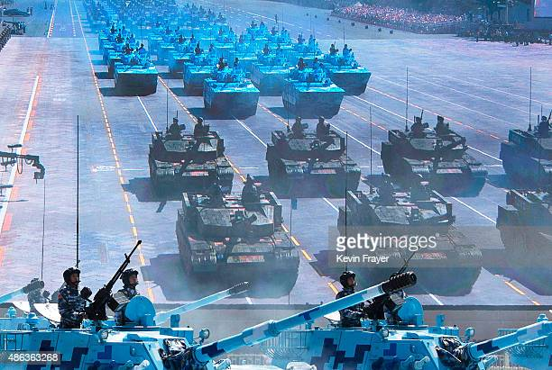 Chinese soldiers ride in tanks as they pass by a large screen at Tiananmen Square during a military parade on September 3 2015 in Beijing China China...