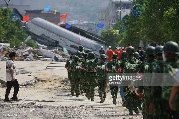 Chinese soldiers run to a collapsed buildings on May 19 2008 in Beichuan Sichuan province China China began three days of national mourning on Monday...