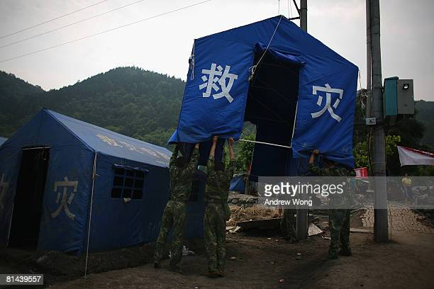 Chinese soldiers set up a tent for earthquake survivors at a refugee camp on June 5, 2008 in Shifang, Sichuan province, China. More than 69,000...